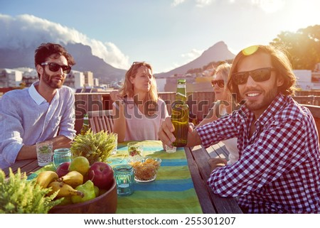 Group of friends sitting hanging out with drinks on the rooftop