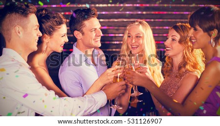 Group of friends toasting glasses of champagne against flying colours