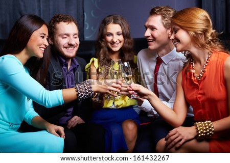 Group of friends toasting with flutes of champagne in the bar