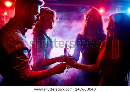 Group of friends with champagne toasting at party in night club