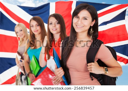 Group Of Happy College Students Standing In Front Of British Flag