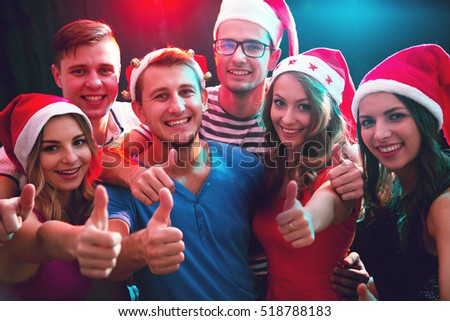 Group of happy friends in santa hats showing OK sign in the night club