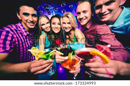 Group of happy friends with cocktails at party