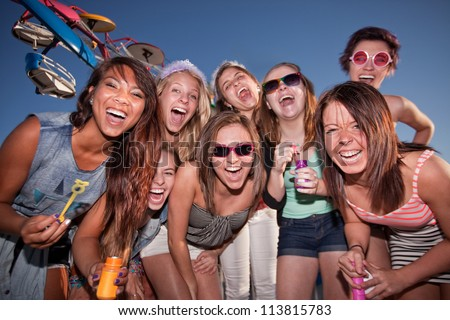 Group of happy girls with bubbles at amusement park