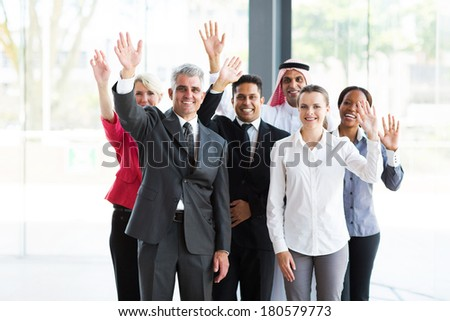 group of happy multicultural businesspeople waving