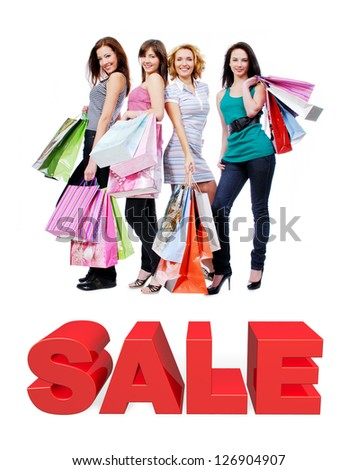 Group of happy women with shopping bags isolated on white. Girls standing on 3 dimensional text.