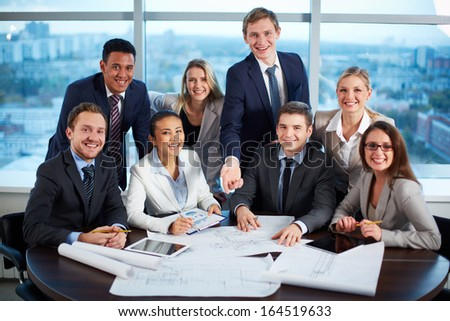 Group of joyful business partners looking at camera with smiles in office