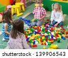 Group of kids playing with colorful constructor on floor - stock photo