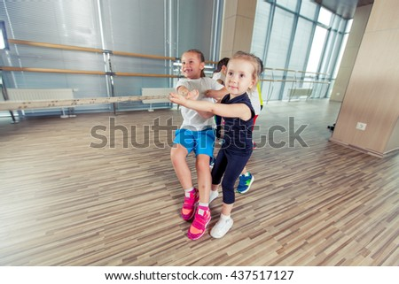 Group of kids pulling a rope in fitness room