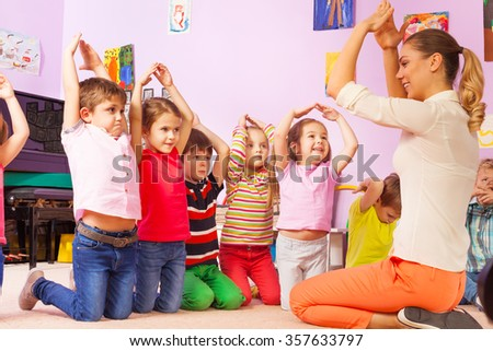Group of kids repeat gesture after the teacher