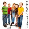 Group of kids singing to microphone standing together, isolate on white - stock photo