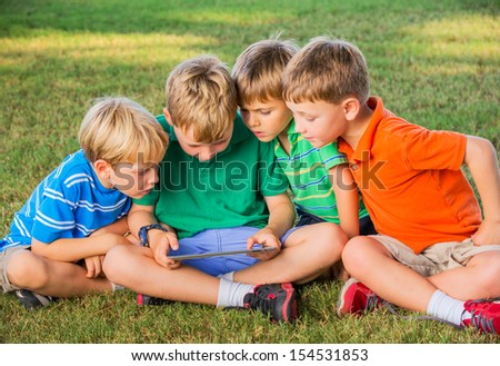 Group of Kids Sitting on grass and using tablet computer