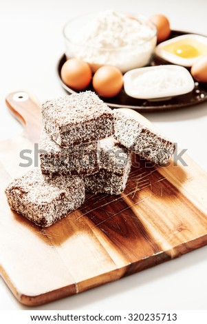 Group of Lamingtons on a timber cutting board with food ingredients in the background