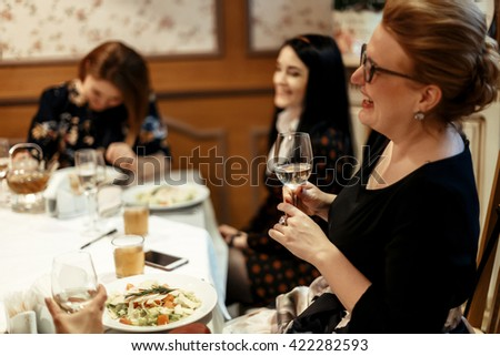 group of luxury elegant women celebrating with champagne and  laughing in rich restaurant
