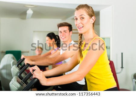Group of men and women train on machine in a fitness club or gym