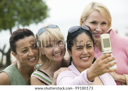 Group of middle-aged women photographing themselves with a mobile phone