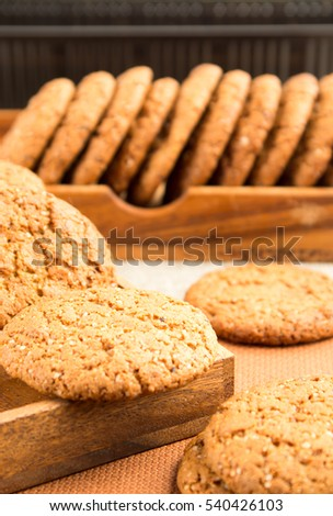 Group of oatmeal cookies on a wooden tray on a brown tablecloth with a very small depth of field