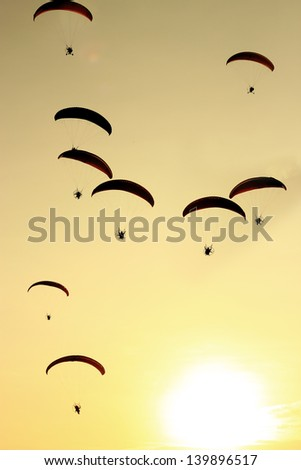 Group of paragliding on the sunset background, Black shadow.