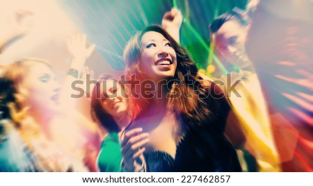 Group of party people - men and women - dancing in a disco club to the music