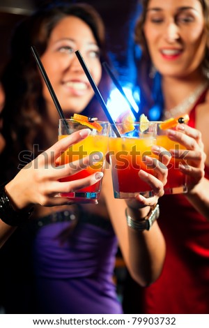 Group of party people - two friends - with cocktails in a bar or club having fun