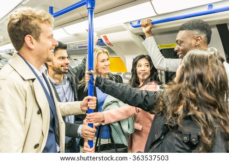 Group of people on tube train in London. They are a mixed group of persons, wearing smart casual clothes. They could be friends or just strangers. Urban lifestyle and transportation concepts.