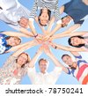 Group of people raise hands in air across blue sky - stock photo