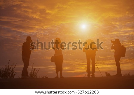 Group of people standing in an open field watching the sunset
