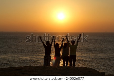 Group of People with Raised Arms looking at Sunset