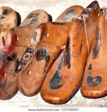 Group of retro style, old wooden shoe pads  on a flea market table. Useful for background.