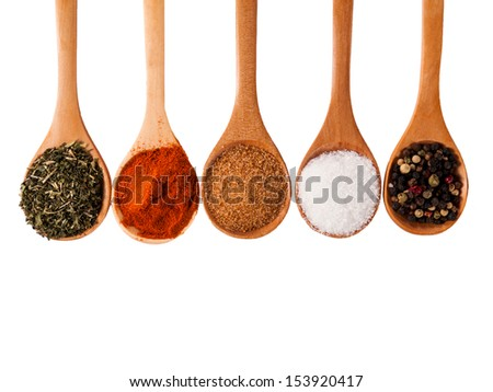 Group of spices in the wooden spoon isolated on white background
