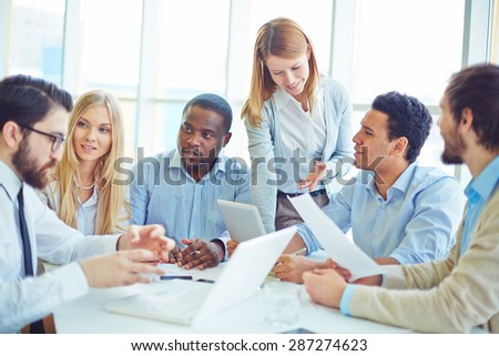 Group of successful professionals communicating in office