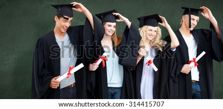 Group of teenagers celebrating after Graduation against green chalkboard