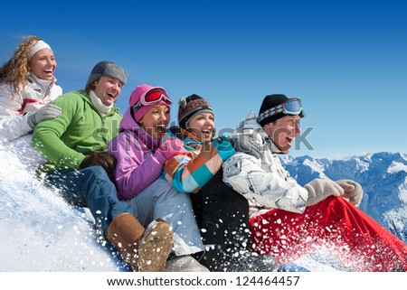 Group of  teenagers slide downhill in winter resort