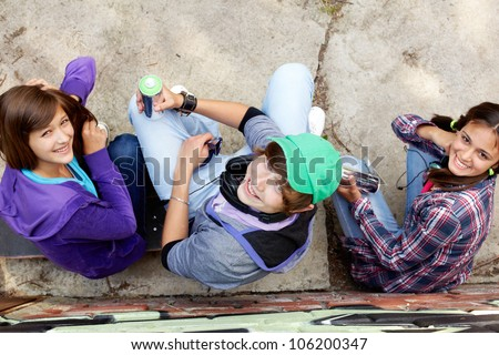 Group of teenagers with aerosol paint sitting and looking up at the camera
