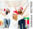 Group of three happy pretty girls are celebrating christmas and new year holidays wearing santa clause red hats and laughing with open arms - stock photo