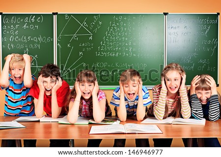 Group of tired school children at a classroom grabing their heads. Education.