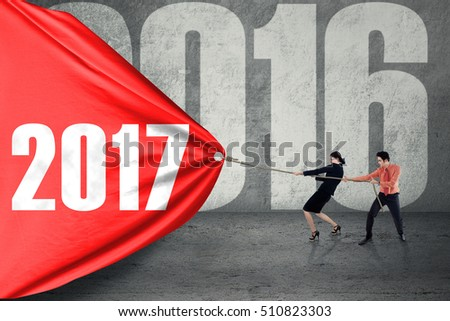 Group of young business people pulling a big red flag with number 2017, symbolizing of business effort for 2017