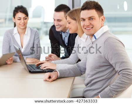 Group of young businessman on meeting.They smiling and looking at camera