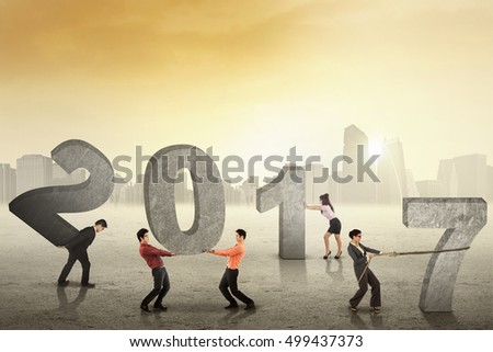 Group of young businesspeople arrange numbers 2017, shot outdoors with bright sunlight