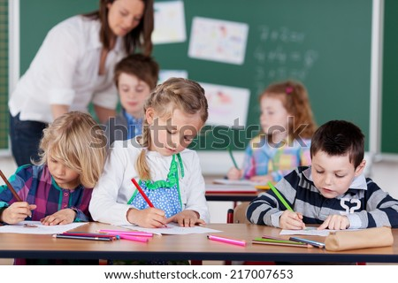 Group of young children studying in kindergarten school with focus to a little boy and two girls drawing with pencil crayons at the front as the teacher works with pupils at the back