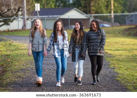 Group of young girls holding hands and laughing while walking on