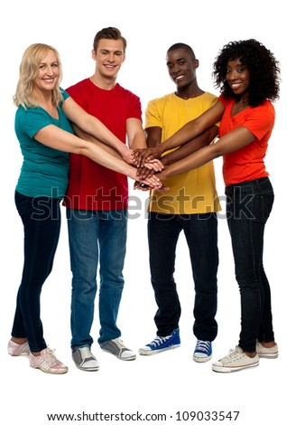 Group of young multicultural friends posing with hands on hands looking at you
