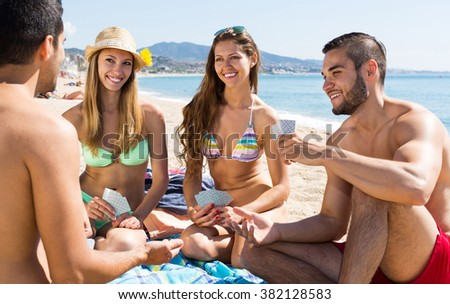 Group of young people playing cards on summer beach
