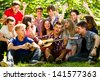Group of young people singing in unison by guitar - stock photo