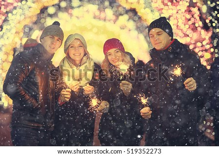group of young people with sparklers Christmas party winter snow city