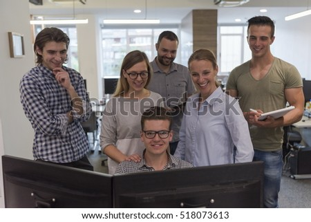 group of young startup business people standing as team at office desk while working on everyday job