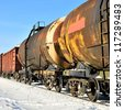 grunge cargo train on the move in winter - stock photo