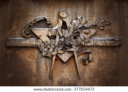 Grunge freemasonry emblem on dramatic background - masonic square and compass symbol, closeup of old architectural building decoration