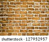 Grungy textured red stone wall inside old neglected and deserted interior, masonry and carpentry brickwork concept - stock photo