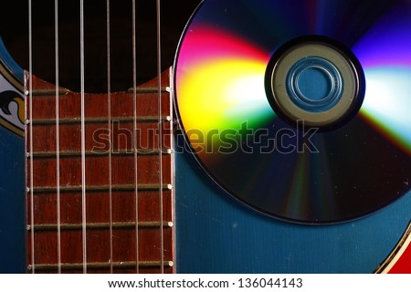 Guitar and CD A photo of a guitar and a cd.